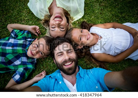 Overhead view of cheerful family lying on grass in yard