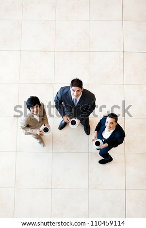 overhead view of colleagues having coffee break at work - stock photo
