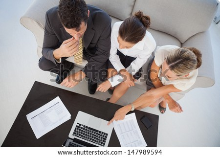 Overhead view of colleagues working together in bright office - stock photo