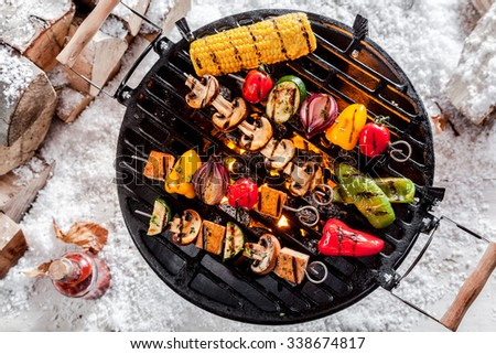 Overhead view of colorful vegetable kebabs and a corncob grilling on a winter BBQ outdoors in snow with tasty spicy dips and the wood pile alongside