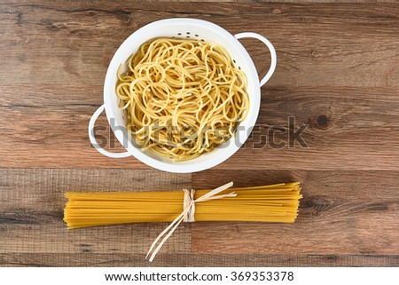 Overhead view of cooked and dried spaghetti. The cooked pasta is in a colander and the raw is tied with raffia. Horizontal on a wood kitchen table. - stock photo