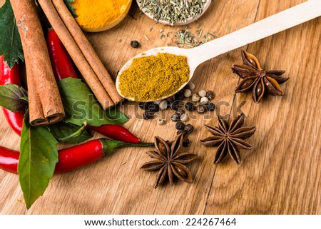 Overhead view of cooking ingredients, spices, herds and oil on a wooden kitchen table.  - stock photo