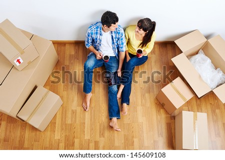 overhead view of couple moving in to new home and using wireless internet on tablet computer - stock photo