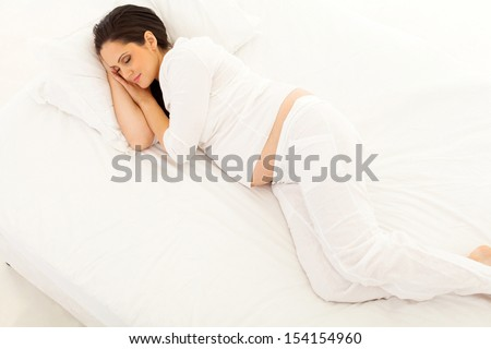 overhead view of cute pregnant woman sleeping on bed - stock photo