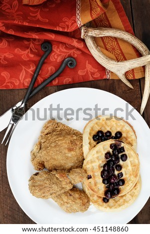 Overhead view of deep fried chicken with waffles served with fresh blueberry sauce over a rustic background.  - stock photo