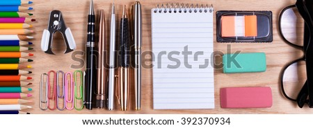 Overhead view of desktop supplies on red oak.   - stock photo