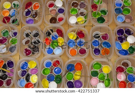 Overhead view of dozens of well used cups of vividly colored acrylic or tempera paint and paintbrushes  arranged in rows of containers.