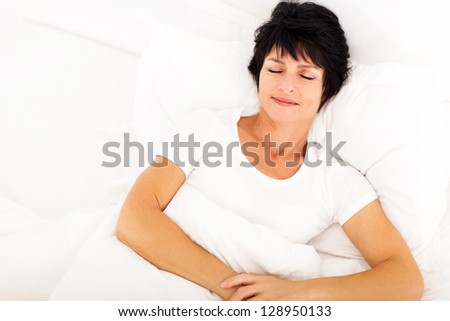 overhead view of elegant middle aged woman sleeping on bed