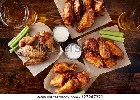 overhead view of four different flavored chicken wings with ranch dressing, beer, and celery sticks - stock photo