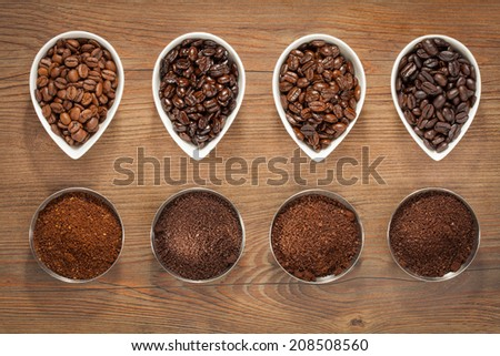 Overhead view of four varieties of roasted coffee beans with their freshly ground counterparts in small bowls on a brown wooden background - stock photo