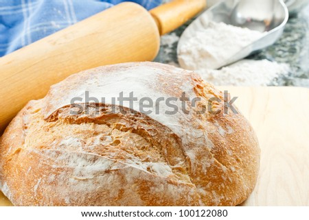 Overhead view of fresh baked artisan bread with enriched wheat flour and rolling pin in the background - stock photo