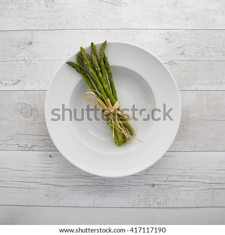 Overhead view of fresh green asparagus on a white plate over a retro wooden background