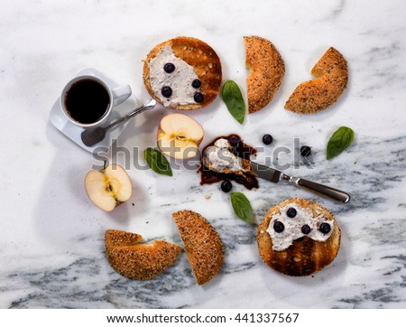 Overhead view of freshly toasted bagels with cream cheese, sauce, blueberries, basil, sliced apple and coffee on white marble stone. Horizontal format.