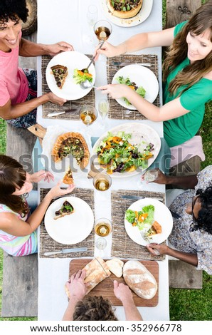 Overhead view of friends passing food at a table, outdoor garden lunch party celebration