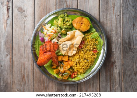 Overhead view of full length Indian biryani rice on wooden dining table background. - stock photo