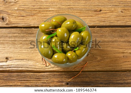 overhead view of green olives in oil, served in glass bowl - stock photo