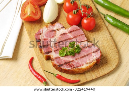 overhead view of grilled pork neck with burned grid, served with the fresh vegetable, on the wooden cutting board - stock photo