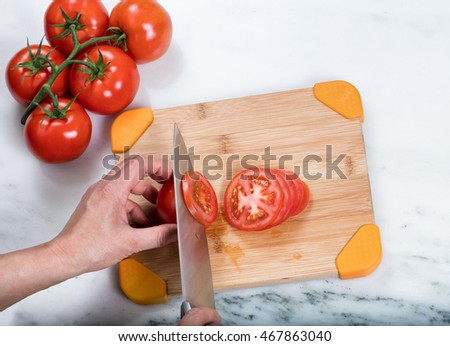 Overhead view of hand slicing a fresh garden tomato with large kitchen knife and whole tomatoes on natural bamboo cutting board.  Selective focus on top of knife and tomato slice.