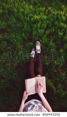 overhead view of hands holding a book.in female hands. against the backdrop of lush young green grass. - stock photo