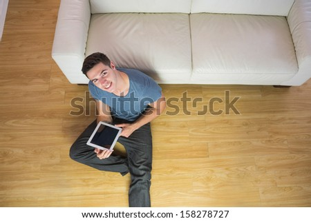 Overhead view of handsome smiling man using tablet in bright living room