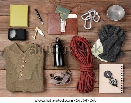 Overhead view of hiking gear laid out for a backpacking trip on a rustic wood floor. Items include, rope, gloves, sweater, carabiners  book, belt, cup, passport, wallet, canteen, compass, money, map, - stock photo