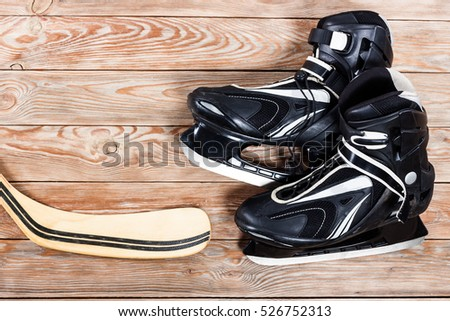 Overhead view of hockey stick and ice skates on old rustic wooden table. Winter sport leisure time concept.