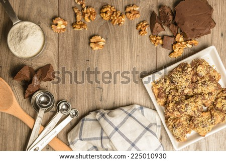 Overhead view of homemade chocolate walnut cookies with ingredients and kitchen utensils on a light rustic wood table. Open space in center for logo or text. - stock photo