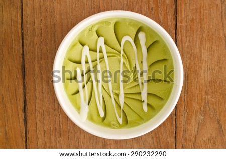 Overhead view of  homemade Green tea  Italian ice cream tub on wooden background - stock photo