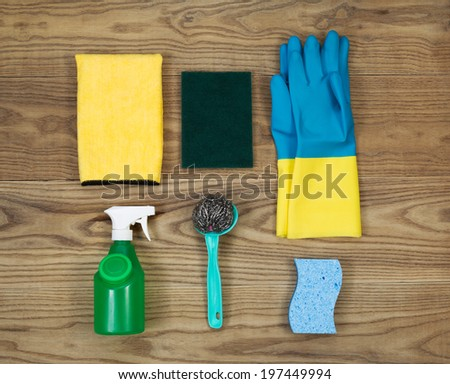 Overhead view of house cleaning materials placed on rustic wood.  Items include sponge, rubber gloves, stainless steel pad, spray bottle, microfiber rag, and scrub pad.  - stock photo