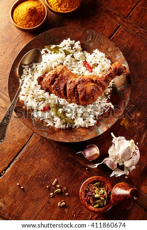 Overhead view of Indian styled spicy chicken tandoori and herbed rice in a round plate on a rustic wooden table besides fresh garlic and curry powder - stock photo