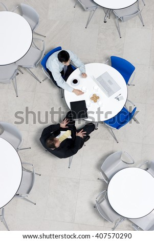 Overhead view of informal business meeting at table of staff canteen - stock photo
