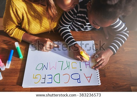 Overhead view of little girl learning the alphabet using coloured crayons