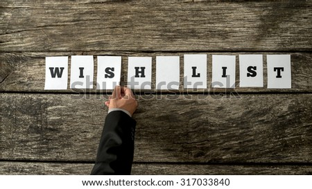 Overhead view of male hand assembling a sign WISH LIST with cards with letters on them on a textured rustic wooden background. Conceptual of personal or organizational wishes, retail and consumerism. - stock photo