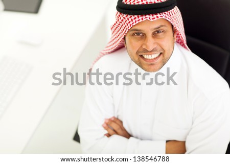 overhead view of middle eastern businessman with arms folded in office