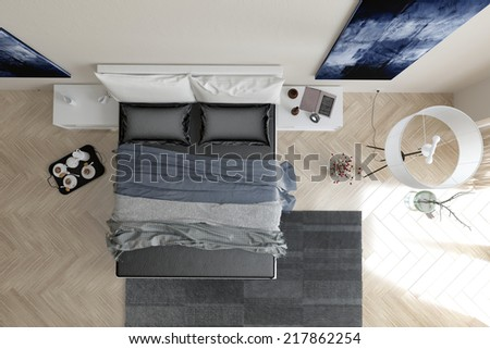 Overhead view of modern grey and white bedroom interior with a double bed with throws and a padded headboard, wall art, grey carpet, lamp and coffee tray on a herringbone pattern parquet floor - stock photo