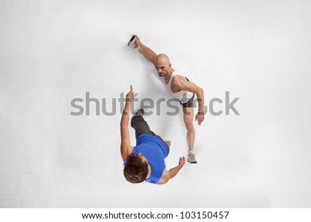 Overhead view of muscular man training with personal trainer