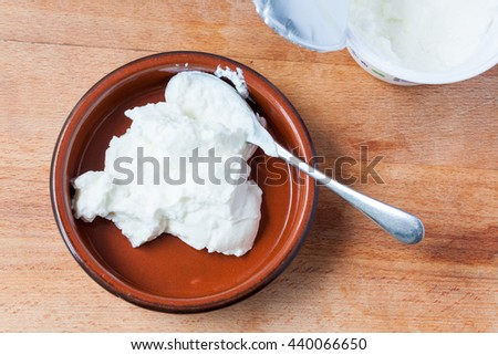 Overhead view of natural greek yogurt in a terracotta dish - stock photo