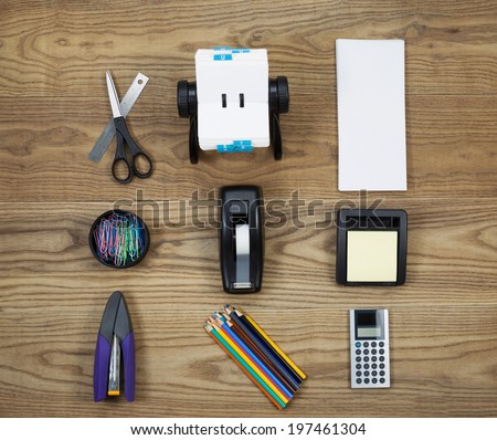 Overhead view of office materials placed on rustic wood.  Items include stapler, scissors, ruler, address book, envelopes, paper clips, tape dispenser, note pad, pencils, and calculator.   - stock photo