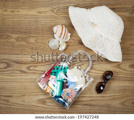 Overhead view of outdoor kit placed on rustic wooden boards.  Items include clear plastic bag, comb, sun screen, hair clips, sea shells, sun glasses and white hat.  - stock photo