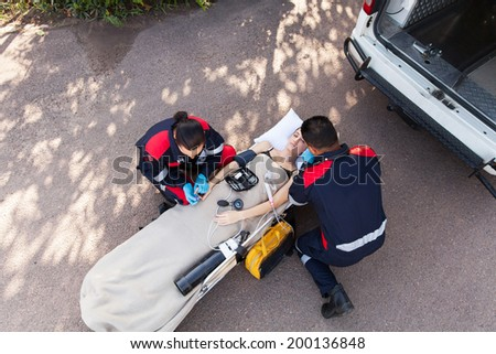overhead view of paramedic team providing first aid to unconscious woman - stock photo