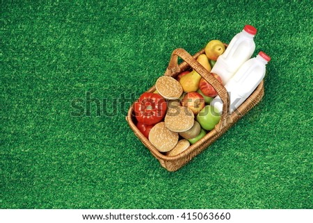 Overhead View Of Picnic Scene. Wicker Basket With Healthy Food And Drinks And Checkered Napkin On The Fresh Summer Garden Grass - stock photo