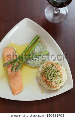Overhead view of salmon dish with asparagus on white plate