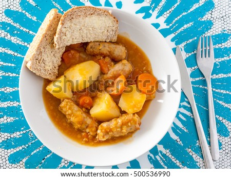 Overhead view of sausage casserole served with potatoes and crusty wholemeal bread