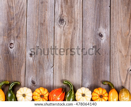 Overhead view of seasonal autumn gourd decorations, lower border, on rustic wooden boards.