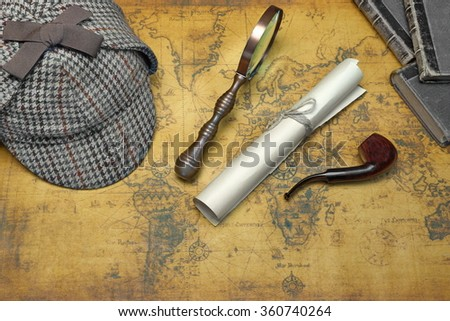 Overhead View Of Sherlock Holmes Deerstalker Hat  And Private Detective Tools On The Old World Map Background. Items Include Vintage Magnifying Glass, Retro Key, Manuscript, Smoking Pipe - stock photo