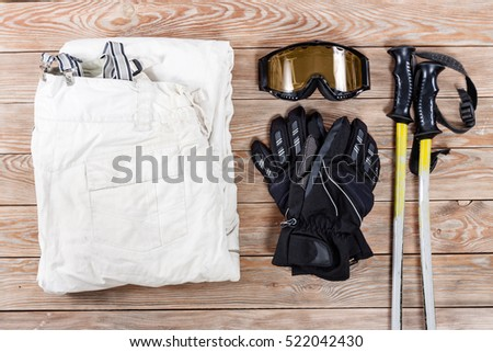 Overhead view of ski and snowboard accessories placed on rustic wooden table. Items included pants, goggles, gloves and ski sticks. Winter sport leisure time concept.