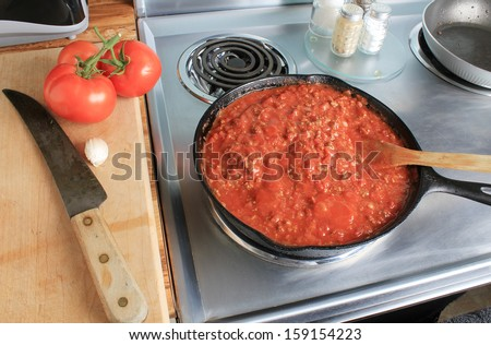 Overhead view of spaghetti sauce in cast iron skillet on stainless steel electric stove.  Fresh tomatoes on cutting board with clove of garlic and kitchen knife.