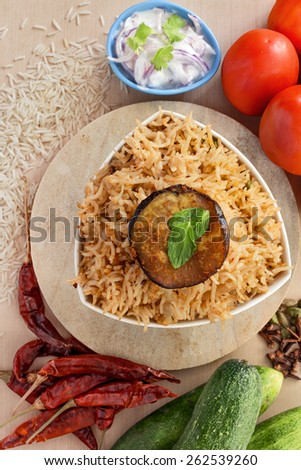Overhead view of spicy Mumbai Tawa pulao with fried aubergine and Onion raita - stock photo