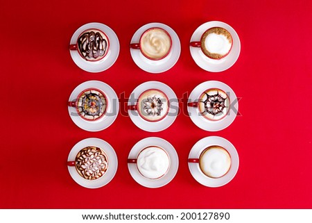 Overhead view of striking patterns and latte art depicted in the foam on espresso or cappuccino coffee in red and white cups and saucers on a red background - stock photo