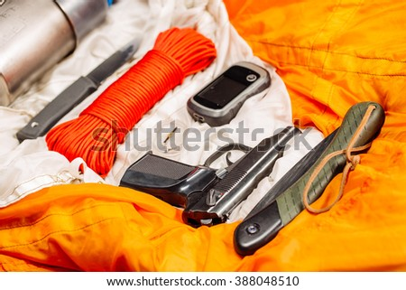 Overhead view of survival gear equipment to survive after plane crash.Items include water flask, knife, red rope, titanium cup, pistol, compact saw,compass, GPS navigator on a orange parachute. - stock photo